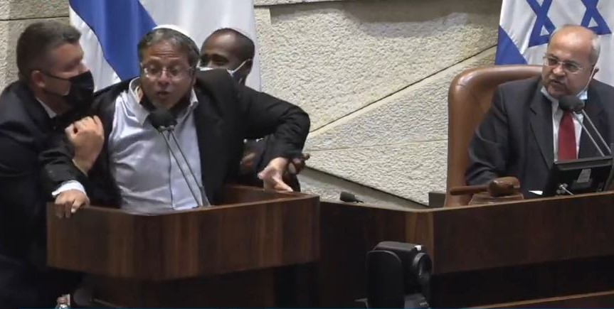 """Racist MK Itamar Ben-Gvir is forcefully removed from the Knesset podium and then ejected from the plenum after calling Joint List MK Ahmed Tibi (right) a """"terrorist"""", July 26, 2021."""