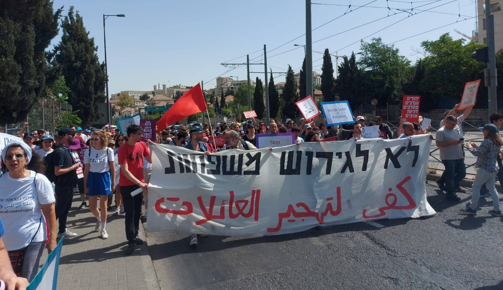 """Demonstrators protest the pending eviction of Palestinian families from their homes in the neighborhood of Sheikh Jarrah in occupied East Jerusalem, June 11, 2021. The large banner reads """"NO to the eviction of families."""""""