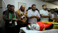 Just before the funeral procession during which confrontations erupted, mourners pray over the body of 11-year-old Mohammad al-Alaama, resident of Beit Ummar, killed by Israeli soldiers, Wednesday, July 28, 2021. Because of the gunfire from the occupation forces, during which Shawkat Khalil Awad, 20, was mortally wounded, Mohammad's body was temporarily abandoned at the grave side until the funeral's attendees could return to give him an improvised, provisional burial.