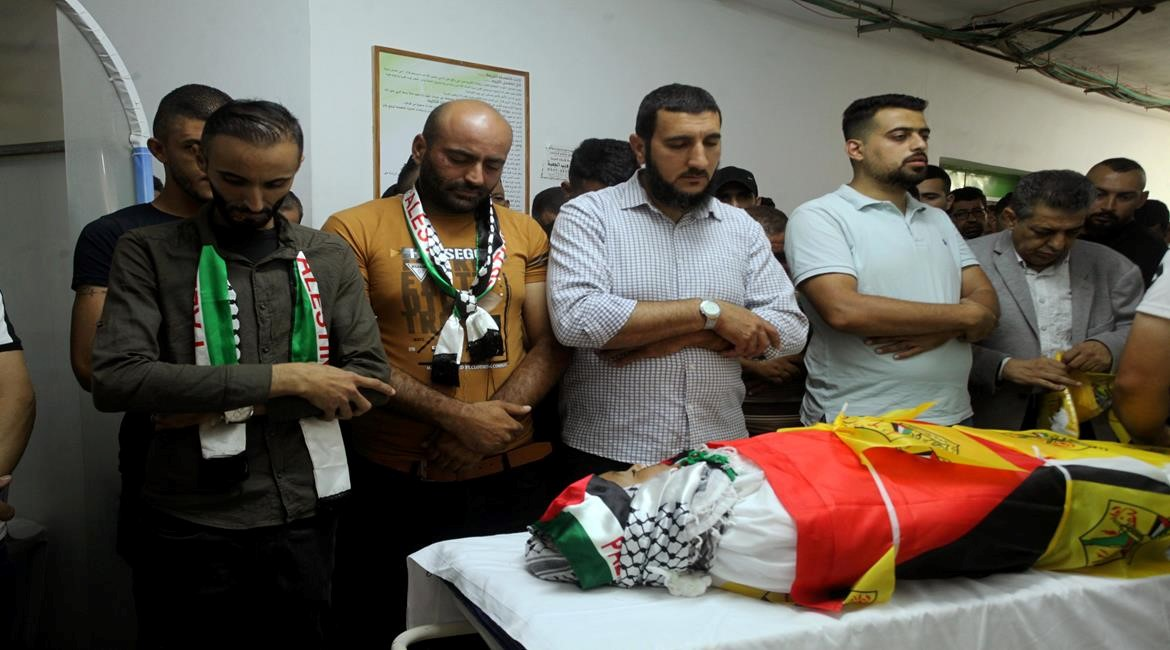Just before the funeral procession during which confrontations erupted, mourners pray over thd body of 11-year-old Mohammad al-Alaama, resident of Beit Ummar, killed by Israeli soldiers, Wednesday, July 28, 2021. Because of the gunfire from the occupation forces, during which Shawkat Khalil Awad, 20, was mortally wounded, Mohammad's body was temporarily abandoned at the grave side until the funeral's attendees could return to give him an improvised, provisional burial.