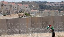 A woman places a Palestinian flag on the barbed wire fence blocking access to the concrete Separation Wall beyond which is Israel's illegal settlement in Modi'in Illit.