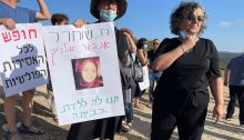 """MK Aida Touma-Sliman (first from right) stands among activists outside the entrance to the Damon Prison in northern Israel calling for the release of Anhar Al-Deek, last Sunday, August 29. The sign in the center with the prisoner's photograph reads """"Free Anhar al-Deek; Let her give birth in her home."""" The sign to the left reads: """"Freedom for all Palestinian women prisoners."""""""