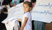 """Palestinian women in Ramallah rally for the release of Anhar Al-Deek so that she can deliver her baby outside prison. The sign in Arabic to the right of the photograph reads in part: """"Your body is in prison, but your spirit is not locked up…"""""""
