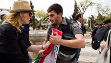 A border policeman confiscates a Palestinian flag from an Israeli demonstrator in occupied East Jerusalem's Sheikh Jarrah neighborhood, March 2015.