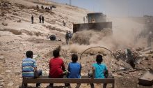 """Children from the Palestinian Bedouin village of Khan al-Ahmar look on as a bulldozer makes preparations for an access road to be used by Israeli forces in the """"imminent evacuation and demolition"""" of the West Bank hamlet, July 4, 2018."""