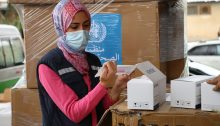 A Palestinian health worker in the West Bank examines medical aid materials provided to the Palestinian people by the UN.