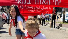 """May Day parade in Nazareth, May 1, 2021. The red banner reads: """"Long live the 1st of May. Workers of the World Unite!"""""""