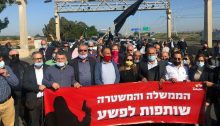 """Leaders and members of Israel's Arab-Palestinian minority protest along Highway 6, the country's major north-south toll road, government inaction in the fight against criminal violence in Arab Society, February 2021. The red banner reads in Hebrew: """"The government and police are partners in the crime."""""""